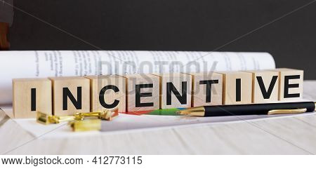 The Word Incentive Is Written On Wooden Cubes Near The Pen And Document.
