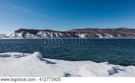 Never Freezing Source Of The Angara River. Blue Water Flows Between The Snow-covered Shores. In The