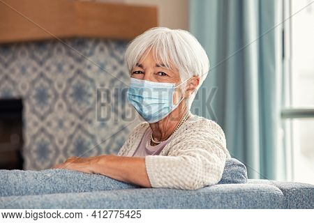 Portrait of smiling old woman wearing face mask at home. Elderly happy grandmother wearing surgical mask and looking at camera during the lockdown due to coronavirus. Beautiful senior healthy lady.
