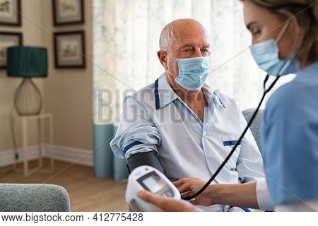 Senior man in pajamas getting blood pressure checked from nurse with face mask for safety against covid19 virus. Nurse checking blood pressure of old patient wearing safety precautions against Covid.