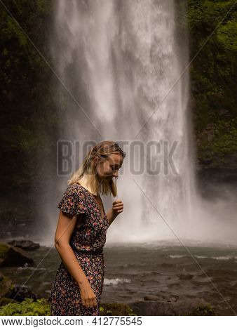 Happy Woman Smiling And Enjoying Waterfall Landscape. Nature And Environment Concept. Travel Lifesty