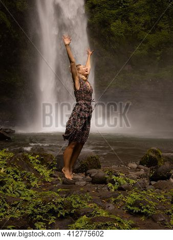 Happy Caucasian Woman Jumping Near The Waterfall. Hands In Motion Movement. Nature And Environment C