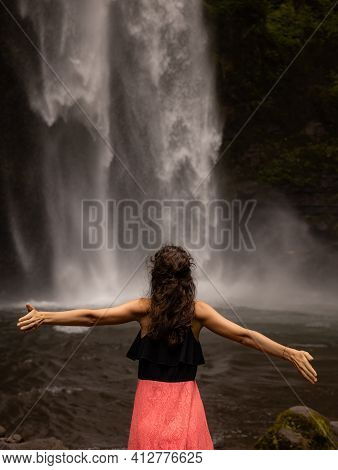 Traveler Woman Wearing Pink Dress At Waterfall. Excited Woman Raising Arms In Front Of Waterfall. Tr