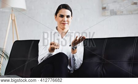 Discouraged Businesswoman Pointing With Hand While Sitting On Sofa In Office.