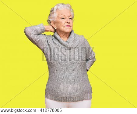 Senior grey-haired woman wearing casual winter sweater suffering of neck ache injury, touching neck with hand, muscular pain