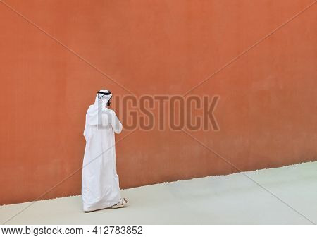 Arabic Man With Traditional Emirates Clothes Walking Outdoors In The Street Against A Orange Wall Ba