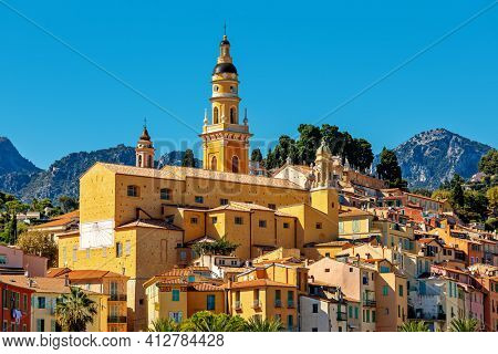 View of colorful houses and belfry of the Saint Michel Archange basilica in old town of Menton - small town on French Riviera.