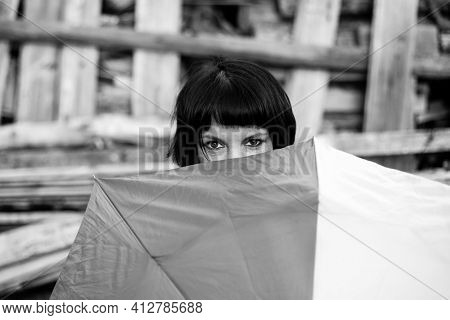 An woman peeping from behind the umbrella. Black and white photo.