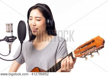 Beautiful Asian Female Singer Playing Guitar And Singing Song By Using Microphone And Pop Filter In