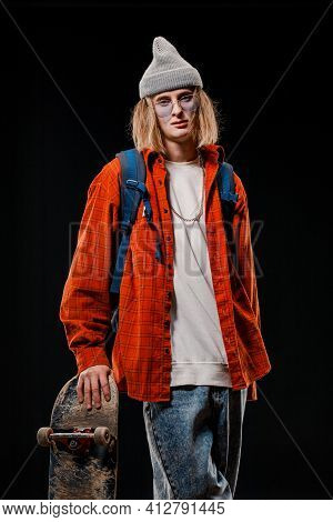 Portrait Of A Stylish Man Holding A Skateboard In The Studio. Close-up Of A Smiling Skateboarder Pos