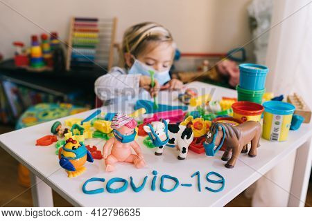 Child Girl In A Protective Mask Playing With Plasticine. Coronavirus Protection Concept. Toys In Pro