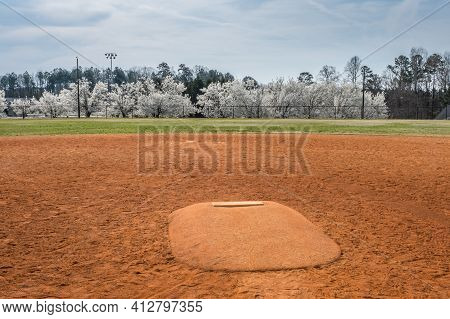 Standing In Front Of A Pitchers Mound Looking Towards The Outfield With White Flowering Trees In The