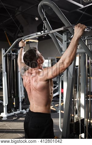 Vertical  Rear View Shot Of A Ripped Muscular Male Athlete Exercising On Lat Pull Down Machine