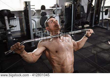 Professional Male Bodybuilder Working Out On Lat Pull Down Machine At The Gym