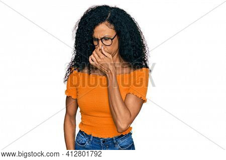 Middle age african american woman wearing casual clothes and glasses smelling something stinky and disgusting, intolerable smell, holding breath with fingers on nose. bad smell