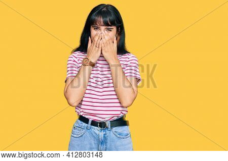 Young hispanic girl wearing casual clothes laughing and embarrassed giggle covering mouth with hands, gossip and scandal concept