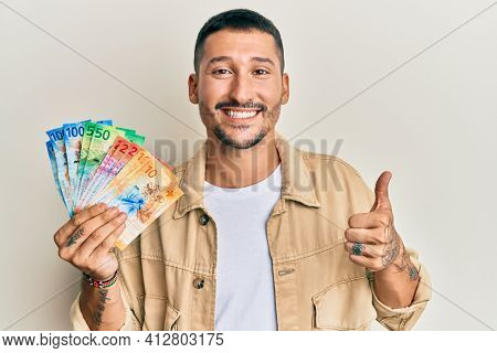 Handsome man with tattoos holding swiss franc banknotes smiling happy and positive, thumb up doing excellent and approval sign