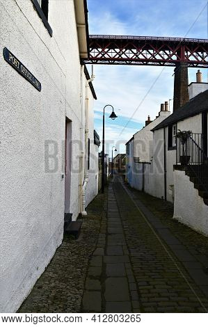 A View Along An Old Cobbled Lane And The Forth Railway Bridge Which Towers Over The Historic Town Of