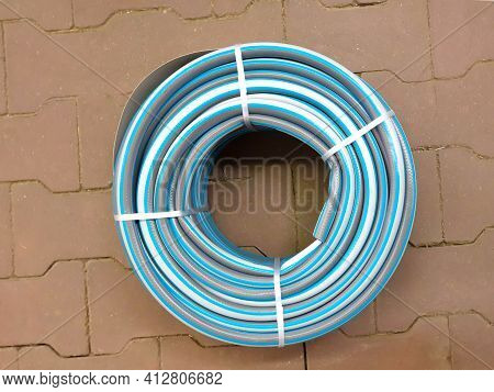 Garden Irrigation Twisted Hose On Tile. Rubber Watering Hose Twisted, Top View.