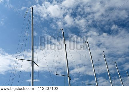 Row Of Silver Yacht Masts In Front Of Blue Sky And White Clouds