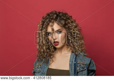Portrait Of Attractive Model Woman With Curly Hairdo On Red Background. Young Lady With Trendy Hair