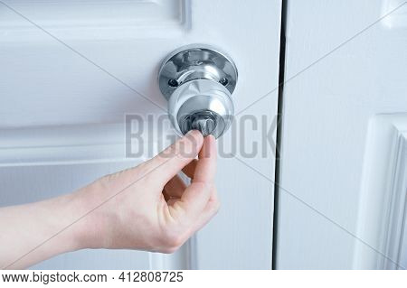 Close-up Hand Opens The Latch On The Doorknob.
