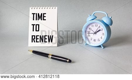On A Light Background, A Notebook With The Inscription Time To Renew, Next To An Alarm Clock And A P