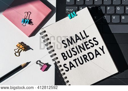 Notebook With Tools And Notes About Small Business Saturday Lies On Laptop.