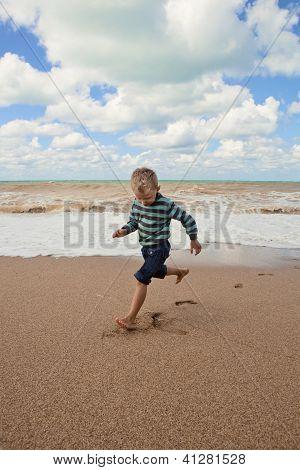 glückliche kleine Junge läuft an der Küste des Meeres