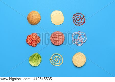 Cheeseburger Ingredients And Sauces Arranged Symmetrically Direct On A Blue Table. Ingredients For A