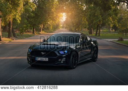 Kherson, Ukraine - July 2018. American Muscle Car Ford Mustang In A Black Color With Blue Headlights