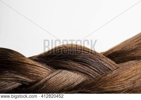 Thick Braid On A White Background. Her Dark Brown Hair Was Pulled Back In A Pigtail. Close-up.brown