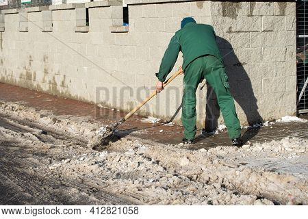 The Landlord Of The District In A Housing Estate In The City Scrapes The Snow Off The Pavement With