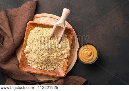 A Wooden Plate With Mustard Powder And Ready-made Mustard In A Cup On A Brown Background. Culinary B