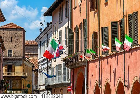 Italian flags waving on the facade and balcony of town hall in Alba, Piedmont, Northern Italy.
