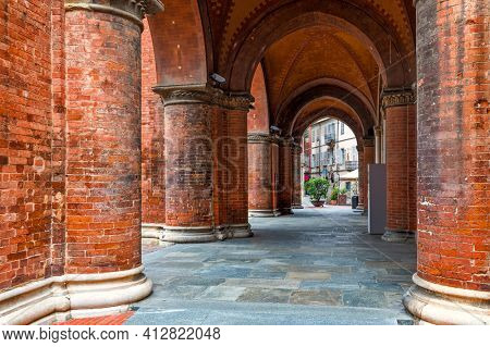 Brick cloister arches at the entrance to San Lorenzo Cathedral (aka Duomo) in small town of Alba, Piedmont, Northern Italy.