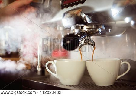 Close Up Of Espresso Pouring From Coffee Machine In Two White Cup. Professional Cappuccino Brewing