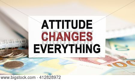 On The Table Are Banknotes, Coins And A Sign That Says - Attitude Changes Everything. Financial And