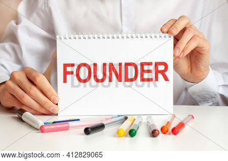 A Sheet Of Paper With Text Jfounder, Multicolored Markers On A White Table. Business And Educational