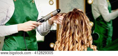 Back View Of Female Hairdressers Hands Curling Womens Hair With Curling Iron In A Hair Salon