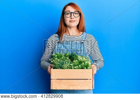 Beautiful redhead woman holding wooden plant pot relaxed with serious expression on face. simple and natural looking at the camera.