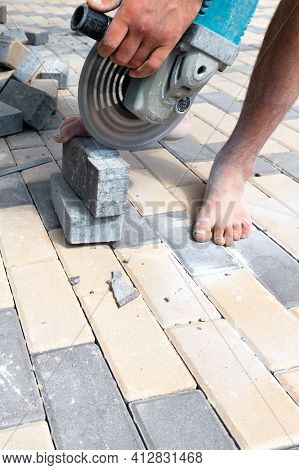 A Worker With A Grinder With A Diamond Cutting Wheel Trims Paving Slabs, Standing Barefoot And Holdi