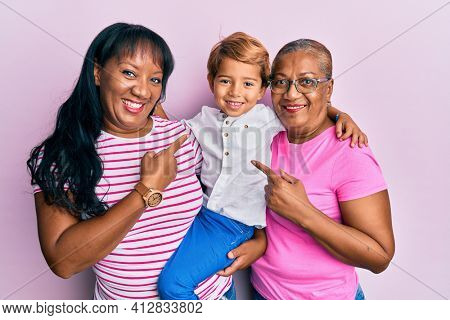Hispanic family of grandmother, mother and son hugging together smiling happy pointing with hand and finger