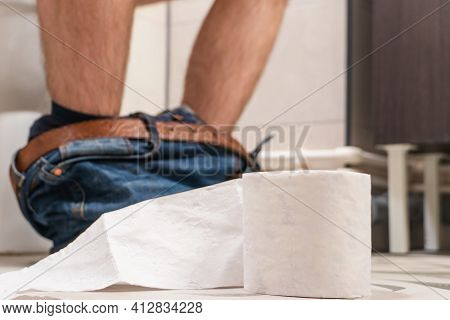 Man Sitting On Toilet Sit Bowl With Toilet Paper, Man Suffering From Diarrhea On Toilet Bowl At Home