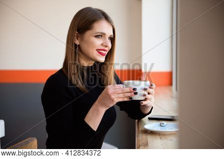 Cheerful Young Woman Drinking Warm Coffee Enjoying It While Sitting In Cafe. Attractive Woman Holdin