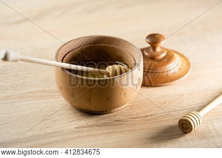 Honey Dripping From Honey Dipper In Wooden Bowl. Close-up. Healthy Organic. Thick Honey Dipping From