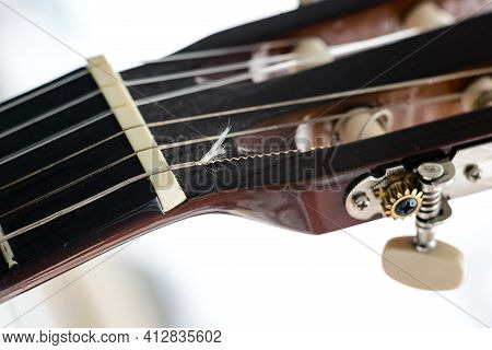 Pegs On The Fingerboard Of A Guitar With A Broken String. Deteriorated And Dusty Acoustic Guitar Hea
