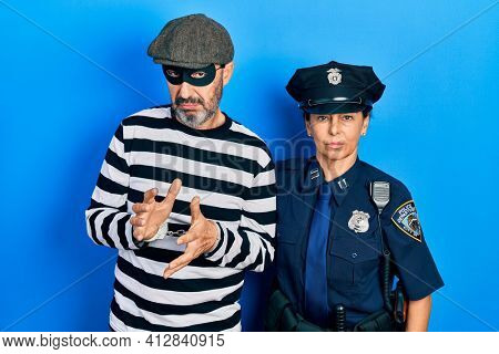 Middle age couple of hispanic woman and man wearing thief and police uniform relaxed with serious expression on face. simple and natural looking at the camera.