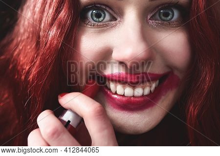 Portrait Of Crazy-looking Teen Girl With Red Hair She Is Smearing Red Lipstick On Her Face, Horror C