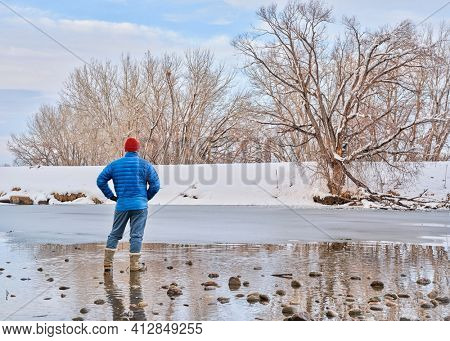male hiker on a shore of partially frozen river - Poudre River in Fort Collins, Coplorado in winter scenery